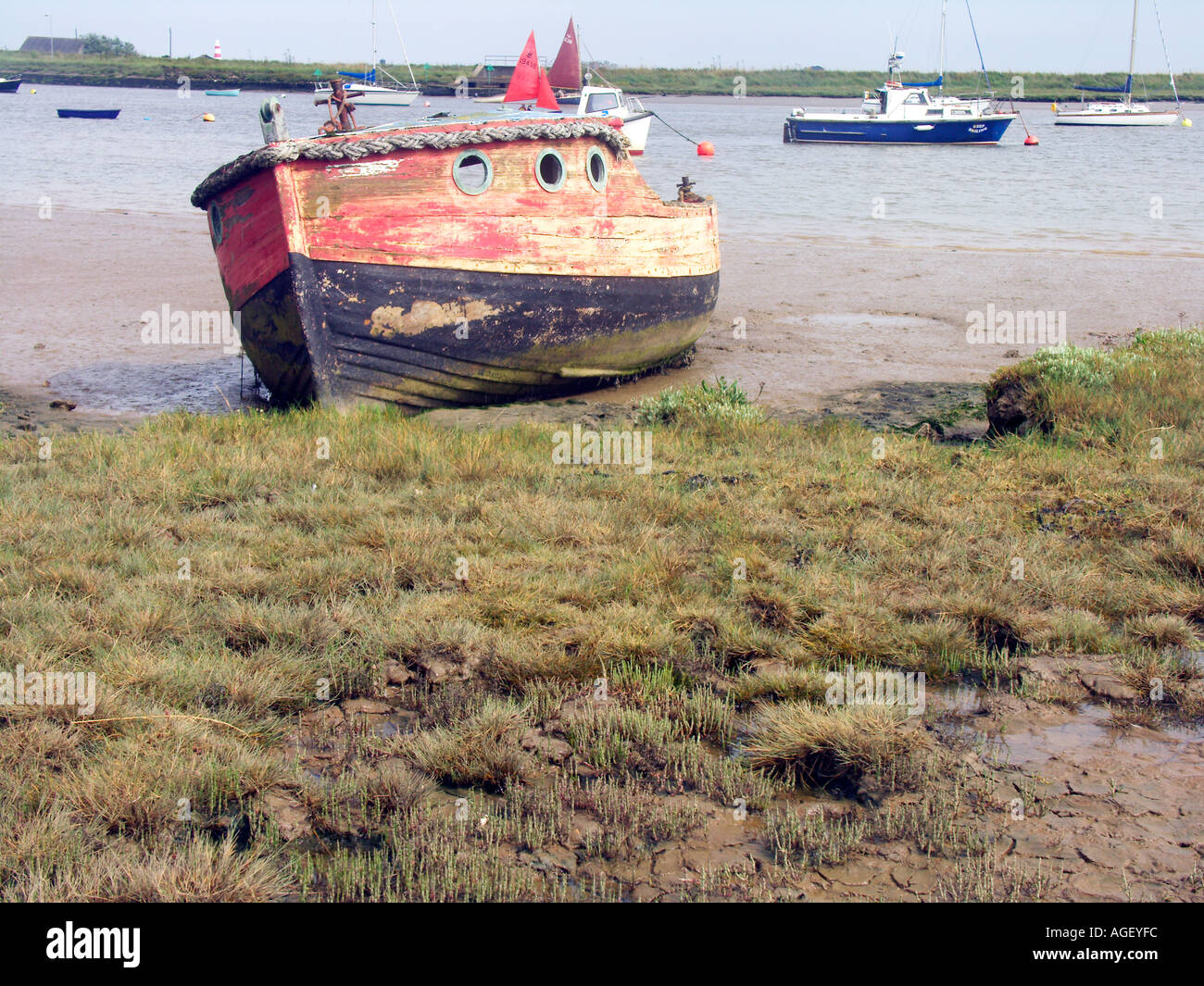 Old red and black boat decaying in mud Orford Suffolk England - Stock Image