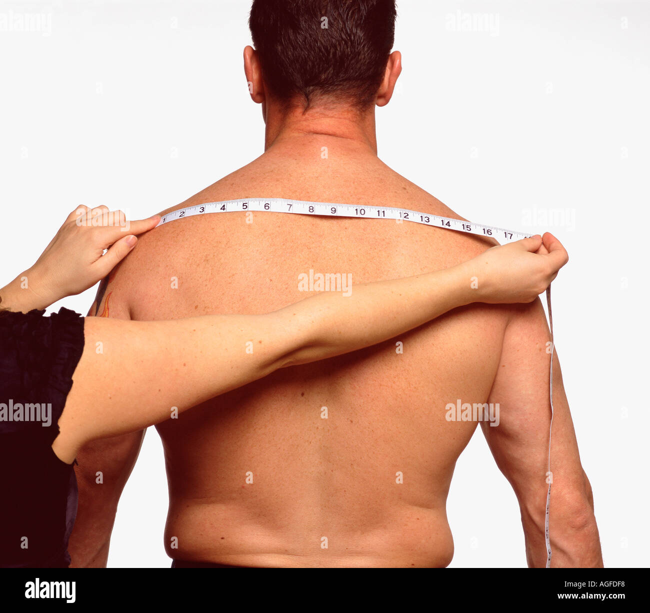 Measuring across male back Stock Photo