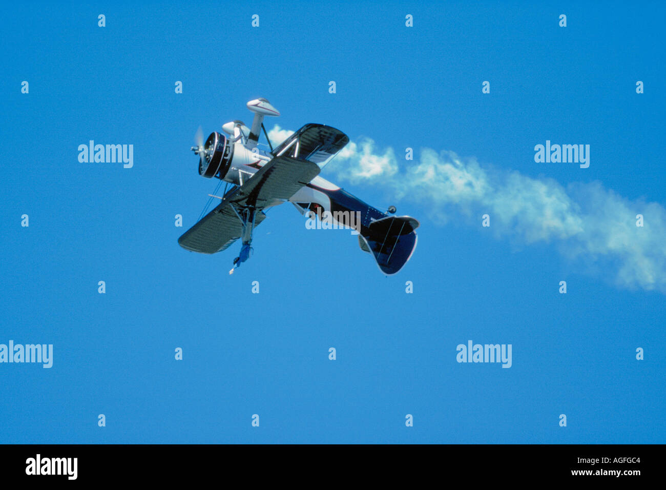 Daring wingwalker upside down during aerial performance - Stock Image