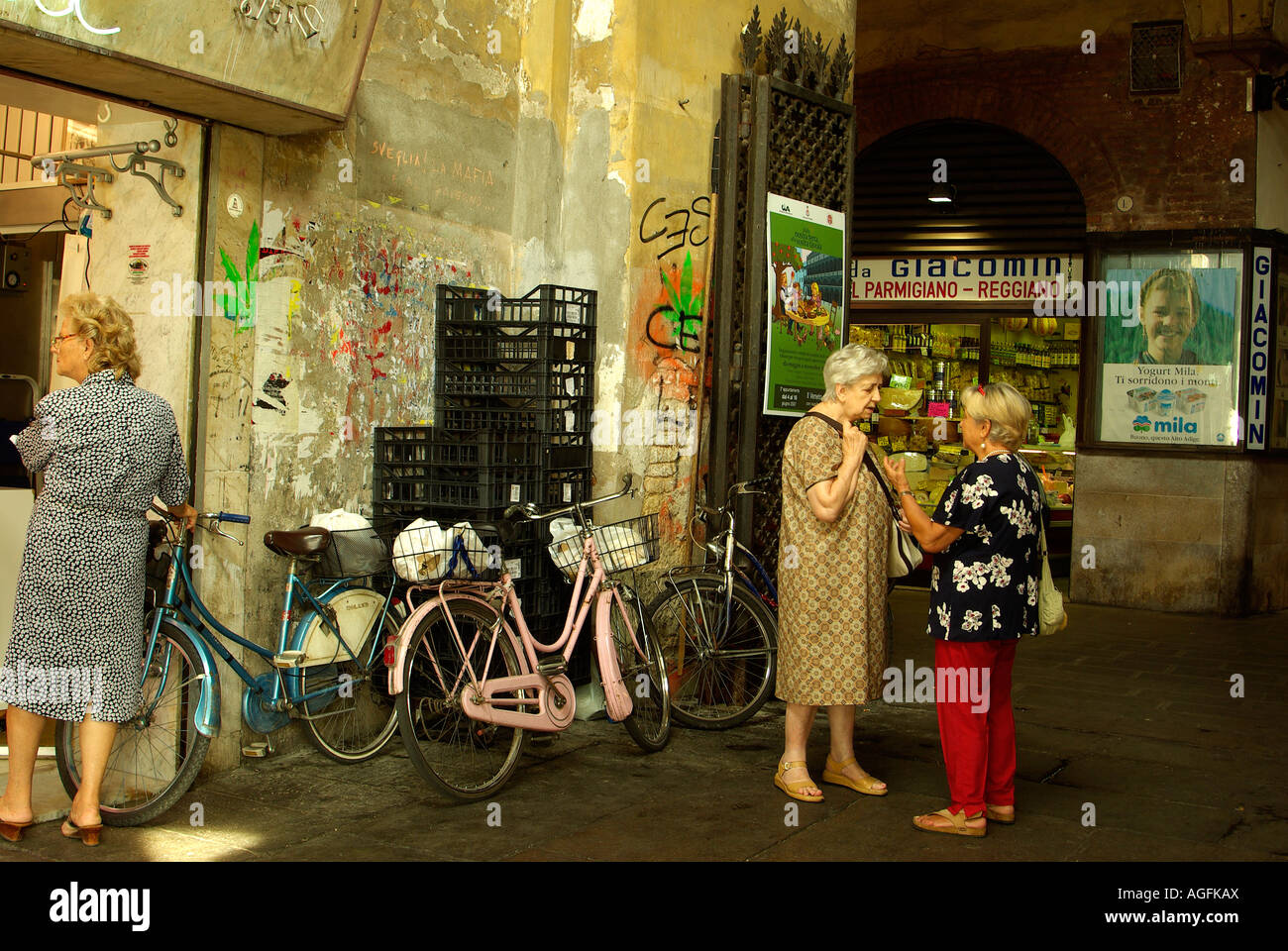 Two women gossiping next to graffiti and a bicycle in the food market of Palazzo della Ragione Padua (Padova) Italy - Stock Image
