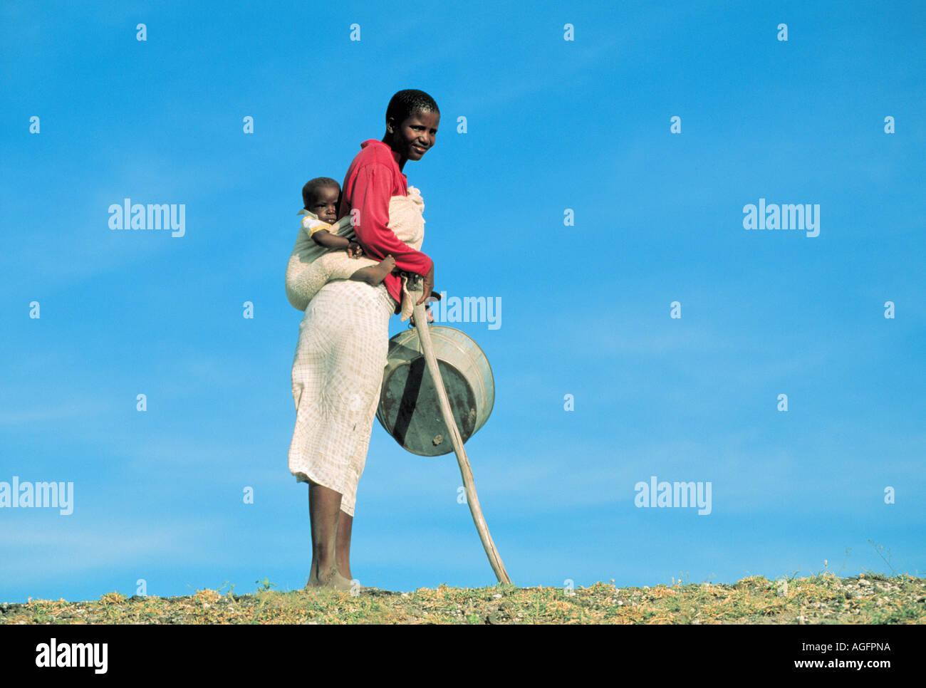 female farmer carrying child on her back, Botswana - Stock Image
