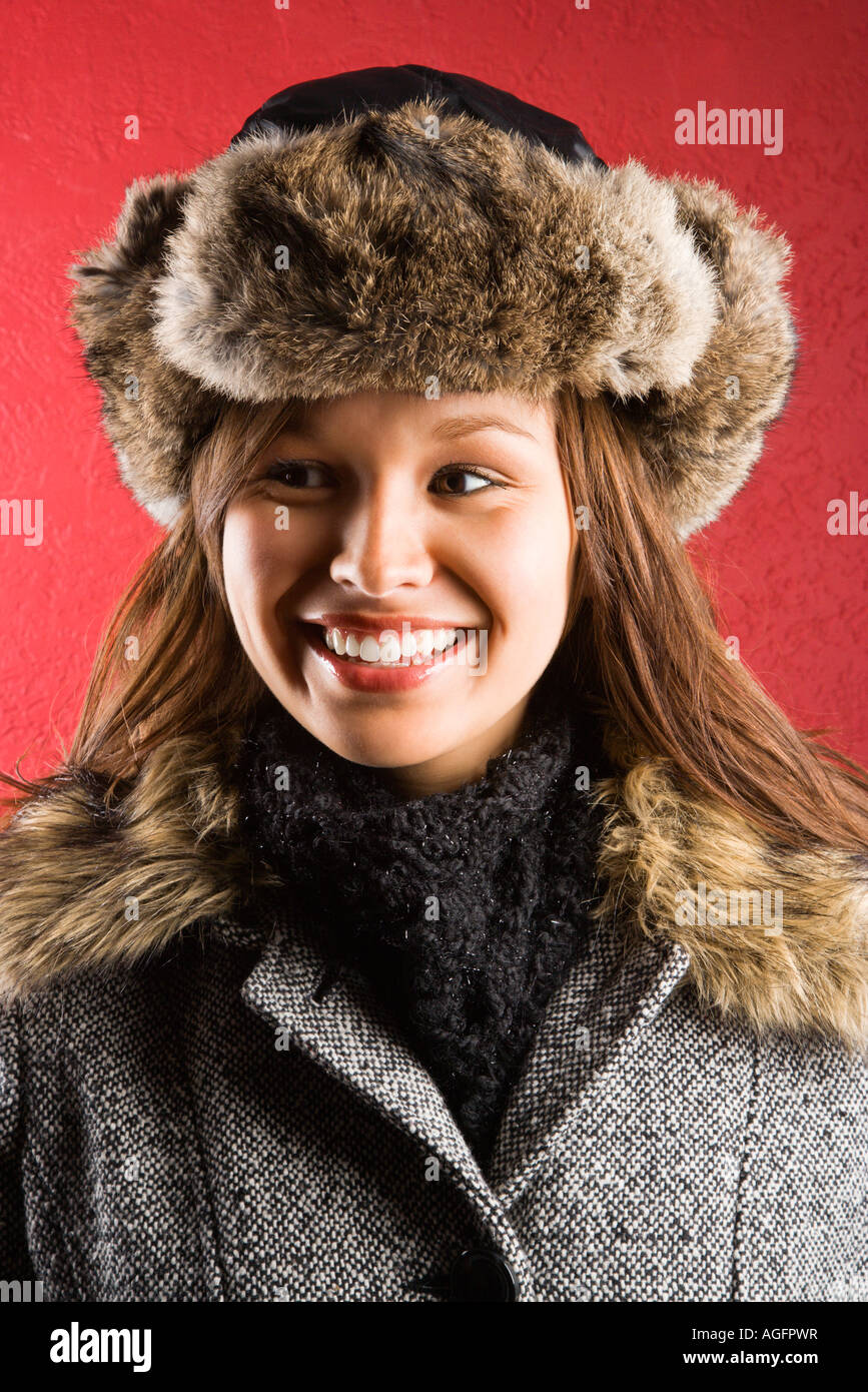 96f92464271 Young adult Caucasian woman wearing fur hat looking to side and smiling -  Stock Image