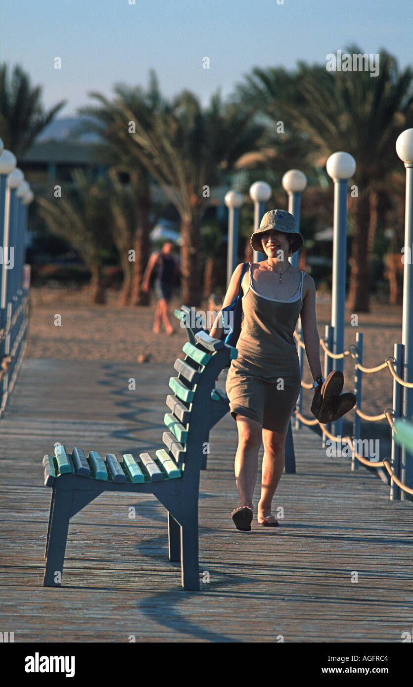 Woman walking towards an empty seat on a jetty Red Sea coast at Nuweiba Sinai Egypt Vacation photograph Middle East - Stock Image