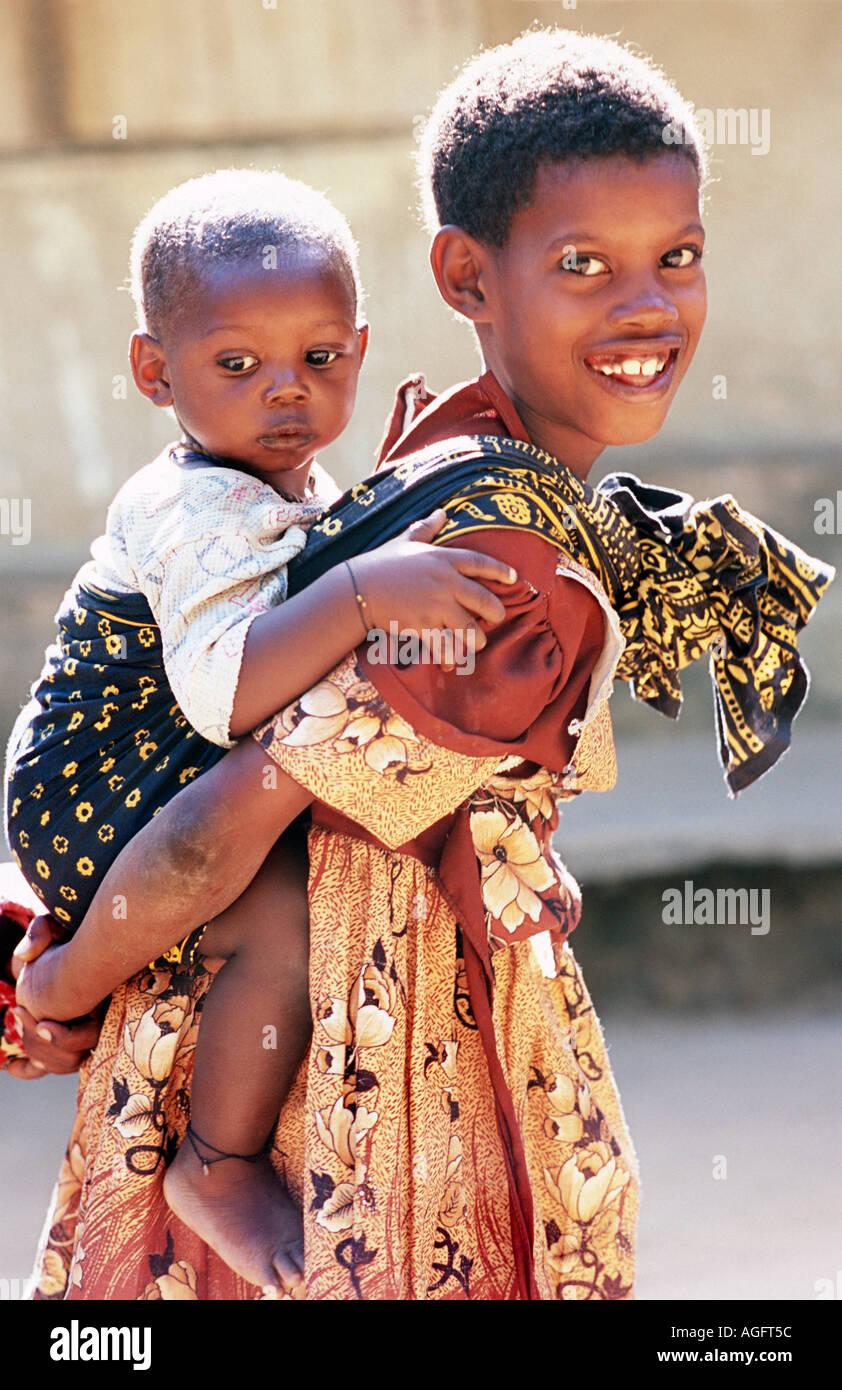 Girl carrying her baby sister on her back Chole island Mafia south of Zanzibar Tanzania East Africa - Stock Image