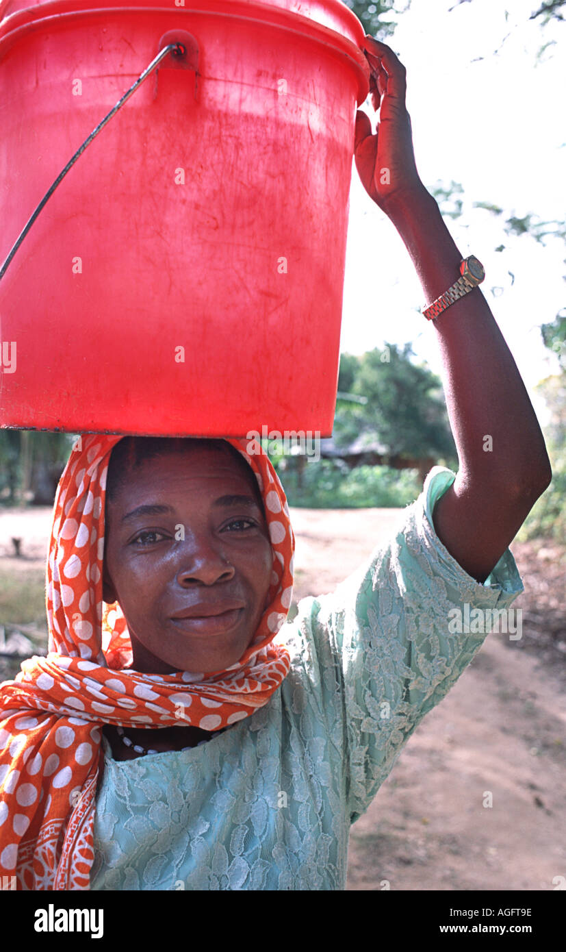 Local woman carrying water Wearing a colourful kanga on her head Chole island Mafia south of Zanzibar Tanzania East Africa - Stock Image