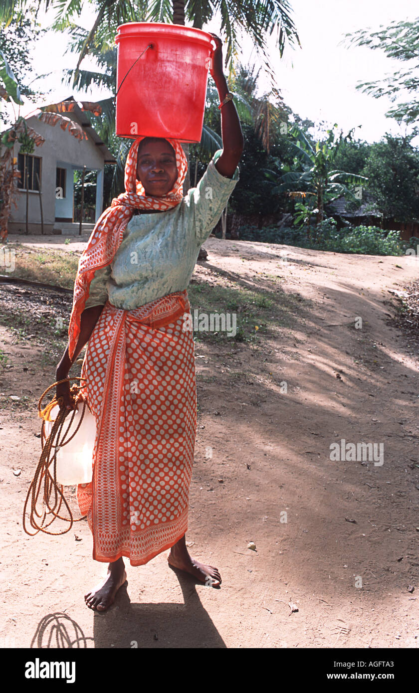 Local woman carrying water Wearing a colourful kanga on her