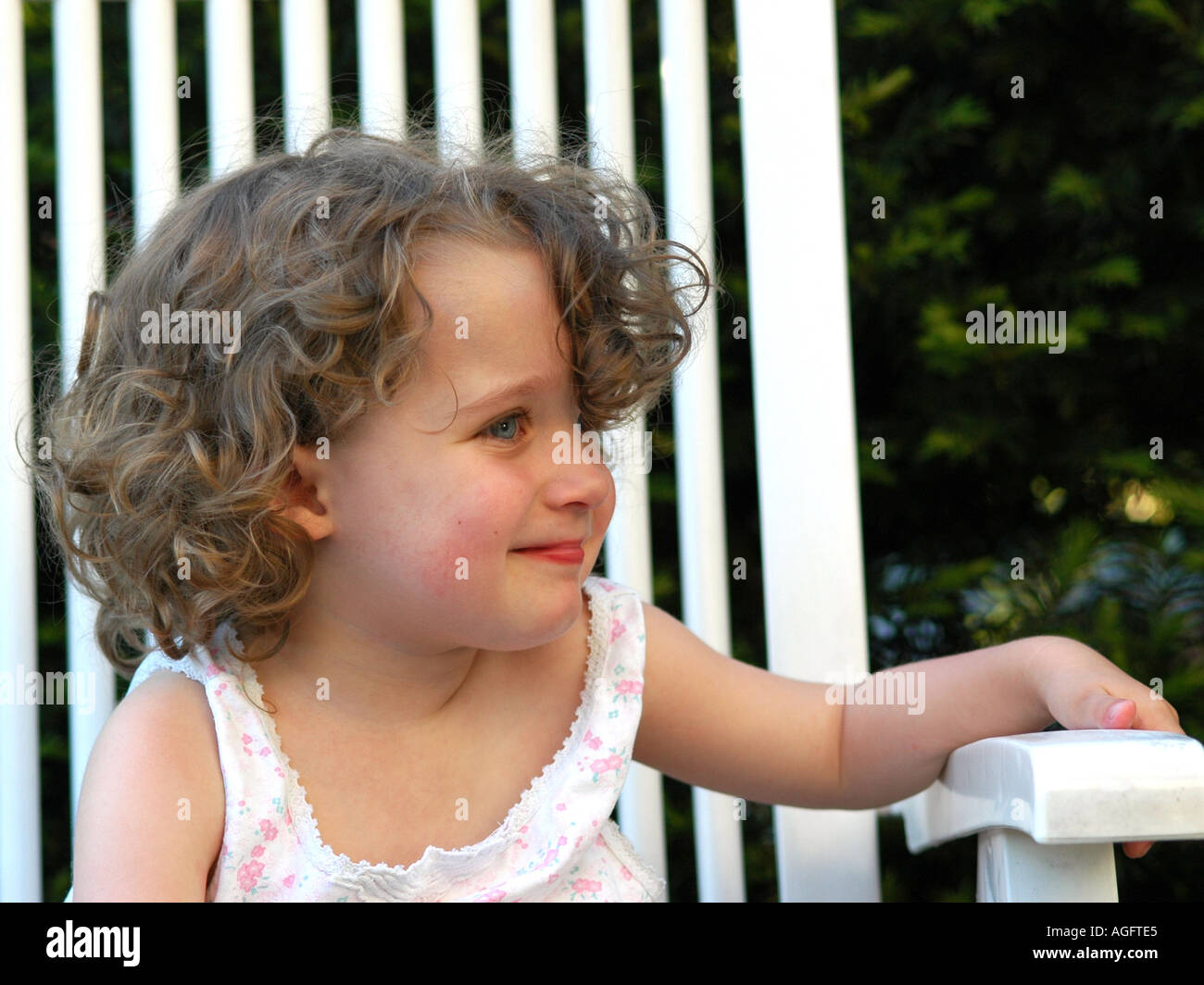 portrait of a female infant sitting on a white chair in the garden - Stock Image