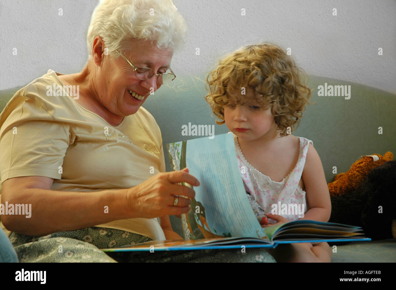 grandmother and child reading a book on a sofa - Stock Image