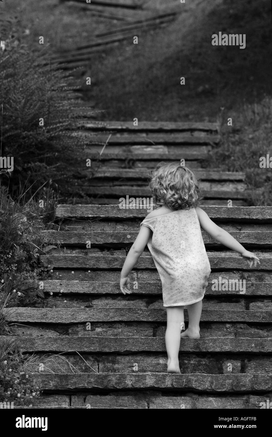 toddler walking up a stairway alone - Stock Image