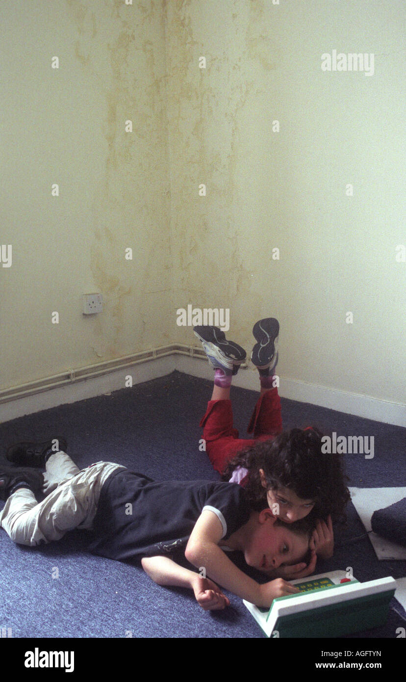 Young child siblings, boy aged 7 and girl aged 9, play with a toy computer in an empty flat with damp walls in the - Stock Image
