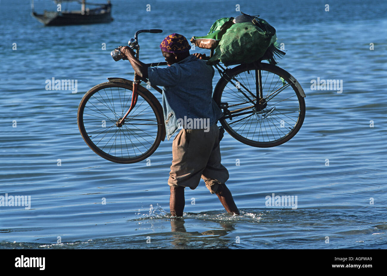 Tanzanian man carrying his bicycle to a boat to transport from Mafia to Chole Island Mafia lies S of Zanzibar East Africa - Stock Image
