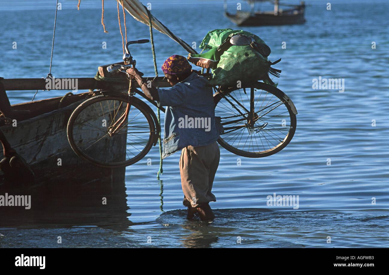 Tanzanian man carrying his bicycle to a boat to transport from Mafia to Chole Island Mafia lies S of Zanzibar Tanzania - Stock Image