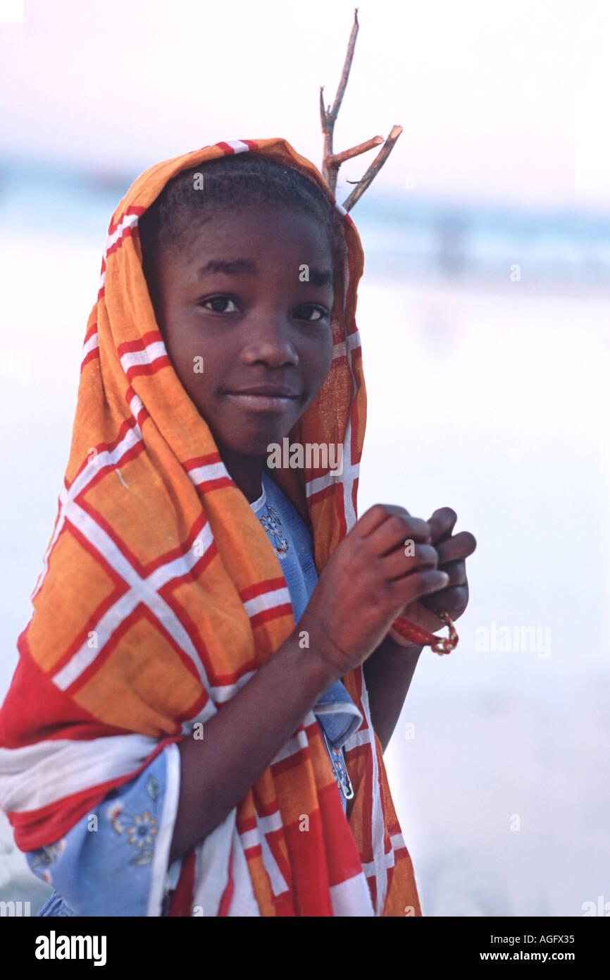 Cheerful Zanzibari girl wearing a kanga cloth over her head Nungwi village Unguja Zanzibar Tanzania East Africa - Stock Image