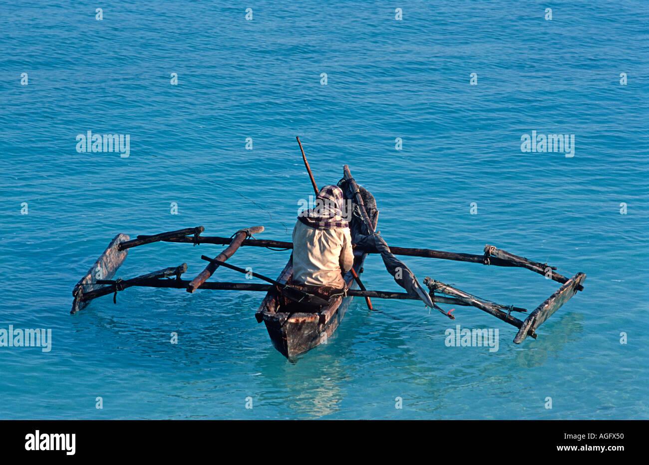 Fisherman in his dugout outrigger canoe Nungwi Unguja Zanzibar Tanzania East Africa - Stock Image