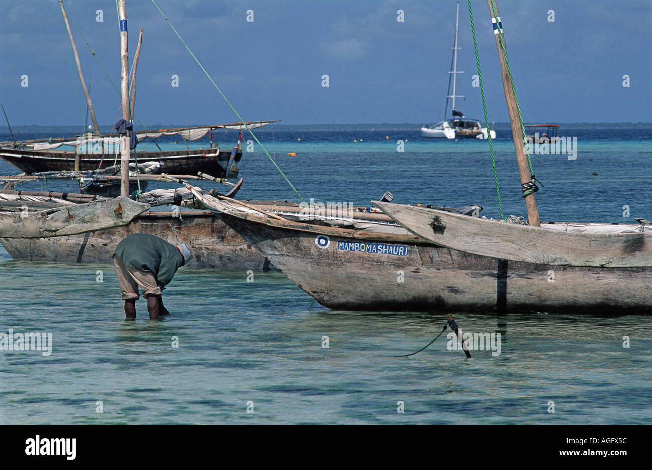 Fisherman in the shallows at low tide beside anchored boats Nungwe Unguja Zanzibar Tanzania East Africa - Stock Image