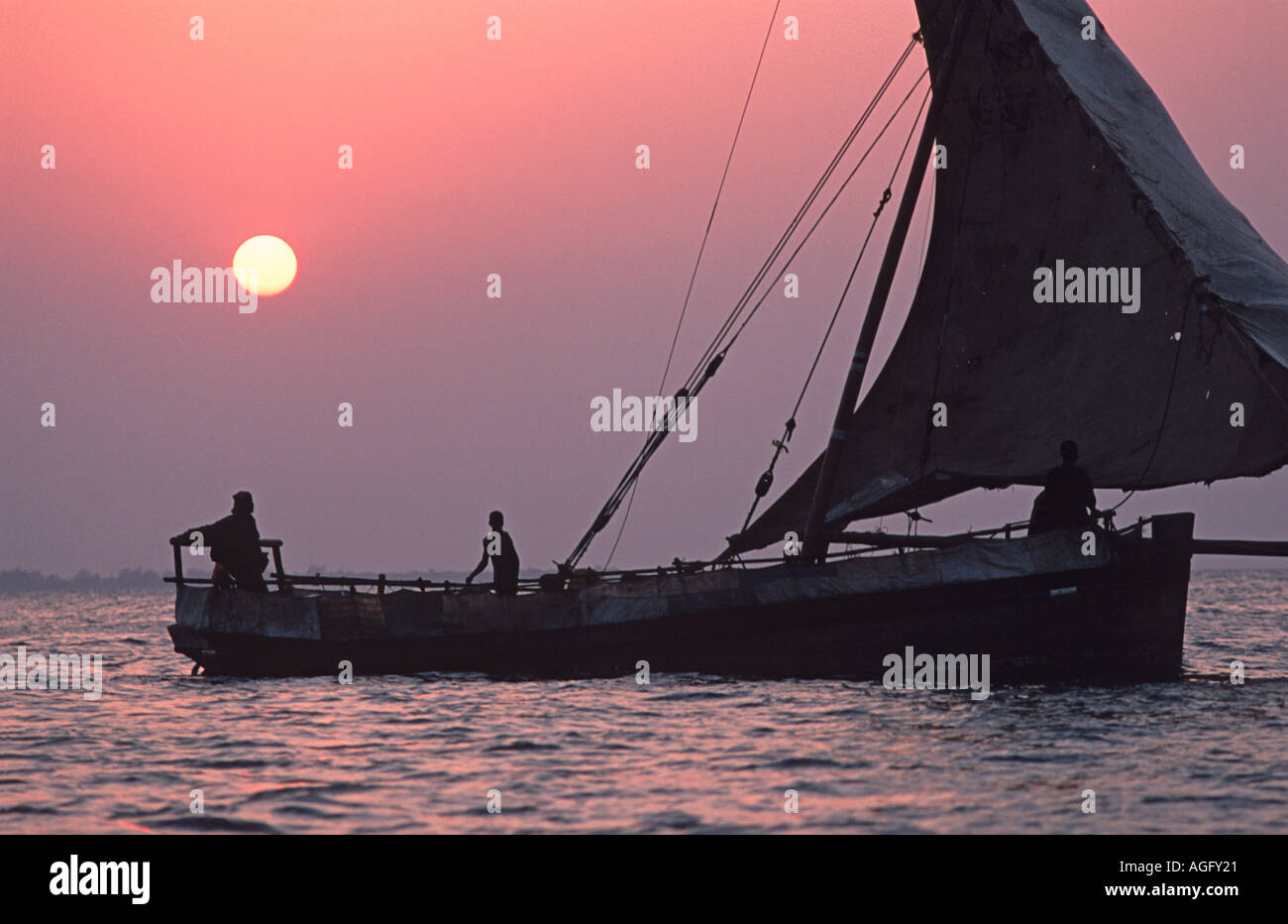 Dhow silhouetted against the setting sun Stone Town harbour Unguja Zanzibar Tanzania - Stock Image