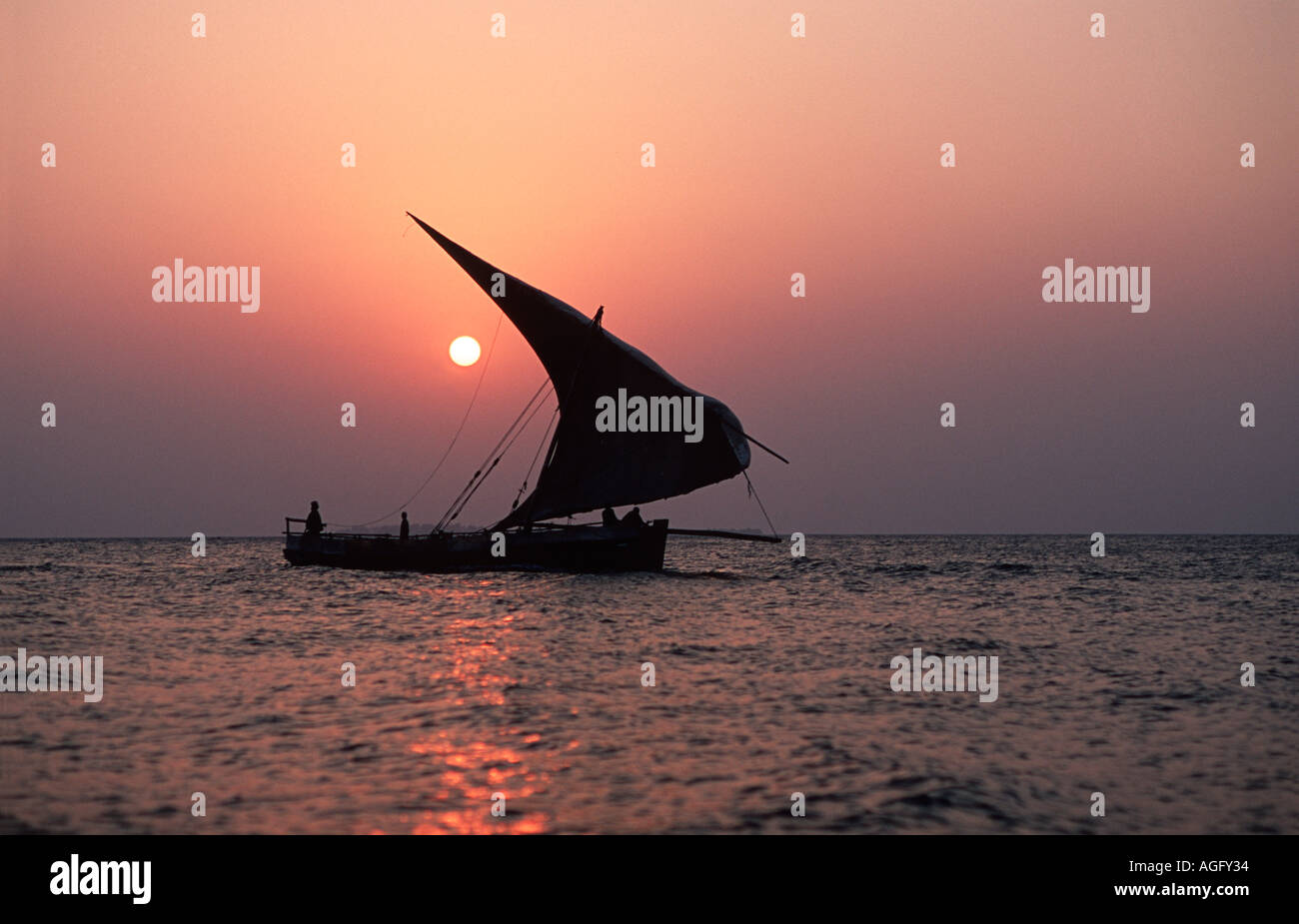 Dhow silhouetted against the setting sun Stone Town harbour Unguja Zanzibar Tanzania East Africa - Stock Image