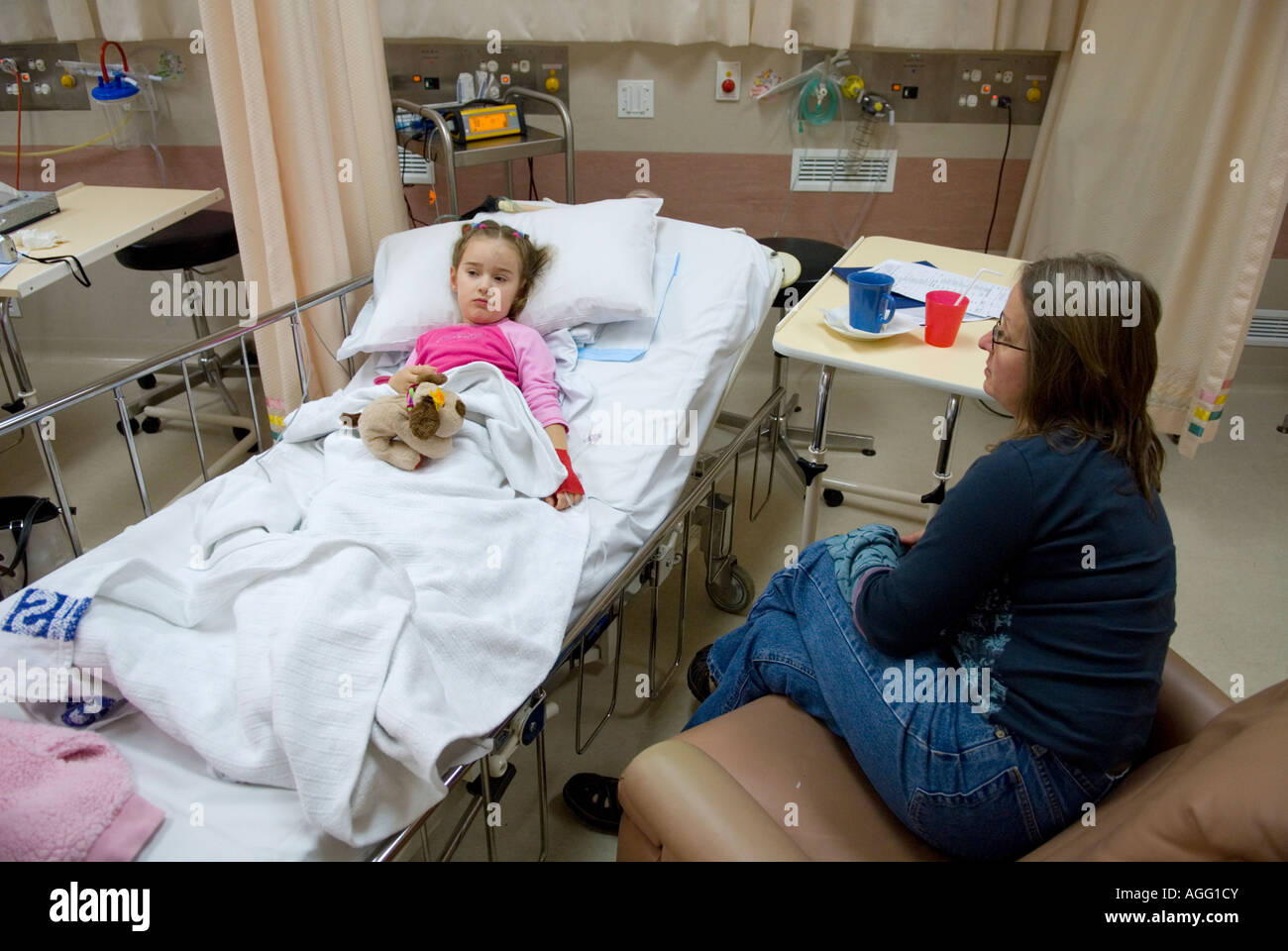 A mother watches over her daughter recovering from general anaesthetic. - Stock Image