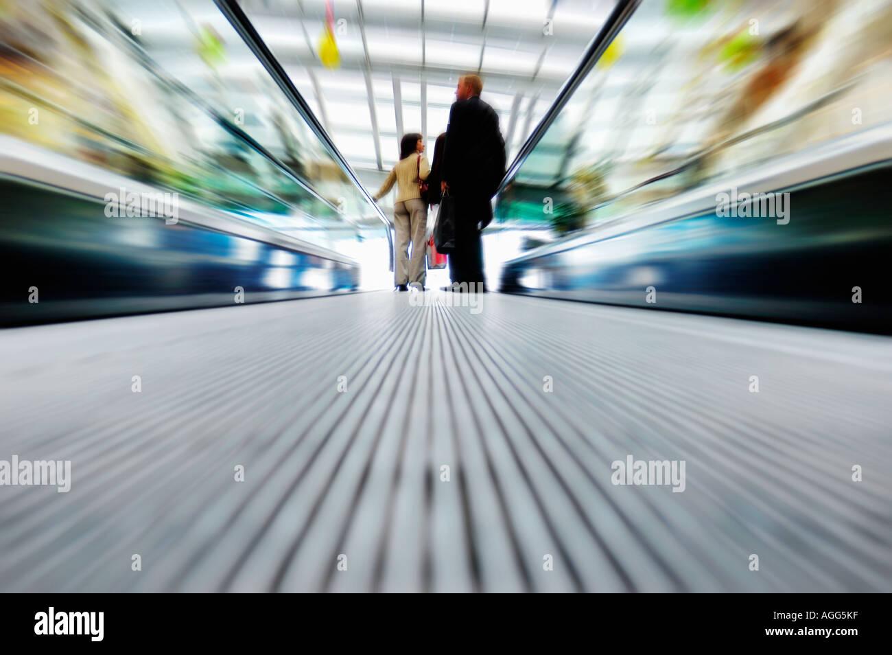 customers on a shopping mall escalator - Stock Image