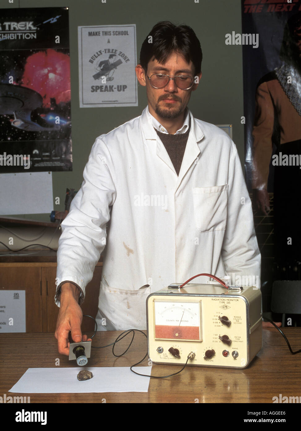 laboratory technician measuring radioactivity of a rock sample with a geiger counter Stock Photo