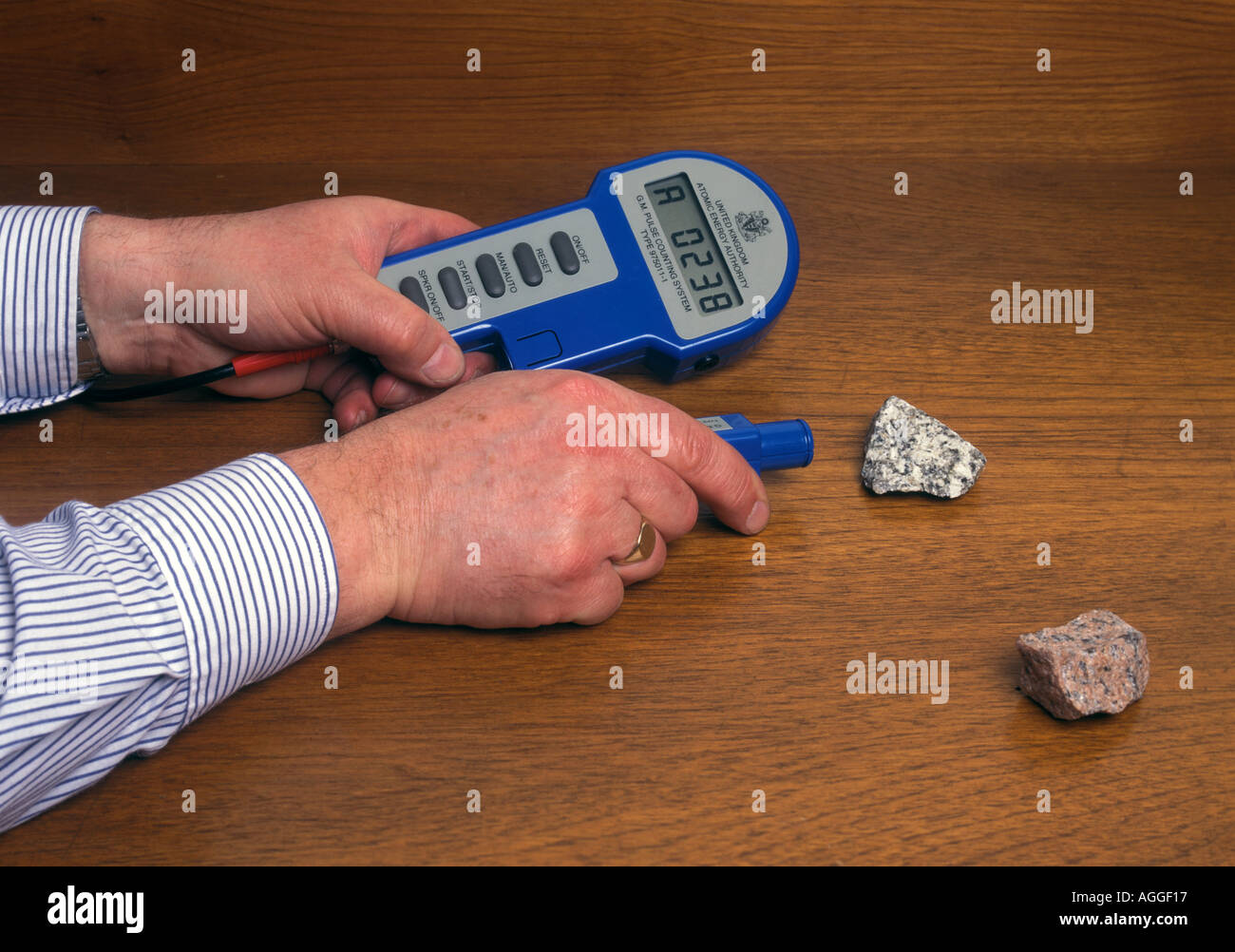 measuring the radioactivity of a rock sample with a geiger counter Stock Photo