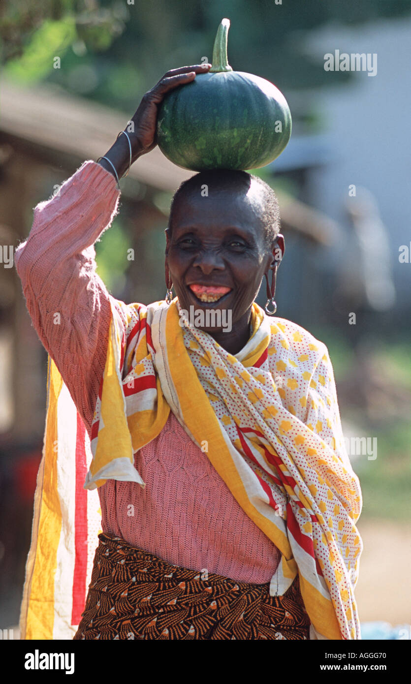 Market vendor with a fresh squash on her head Arusha Tanzania The kanga cloth draped across her shoulders is commonplace - Stock Image