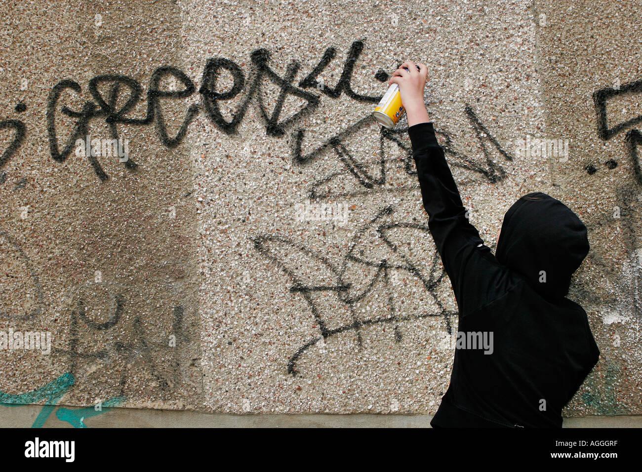 Teenagers spraying graffitti - Stock Image