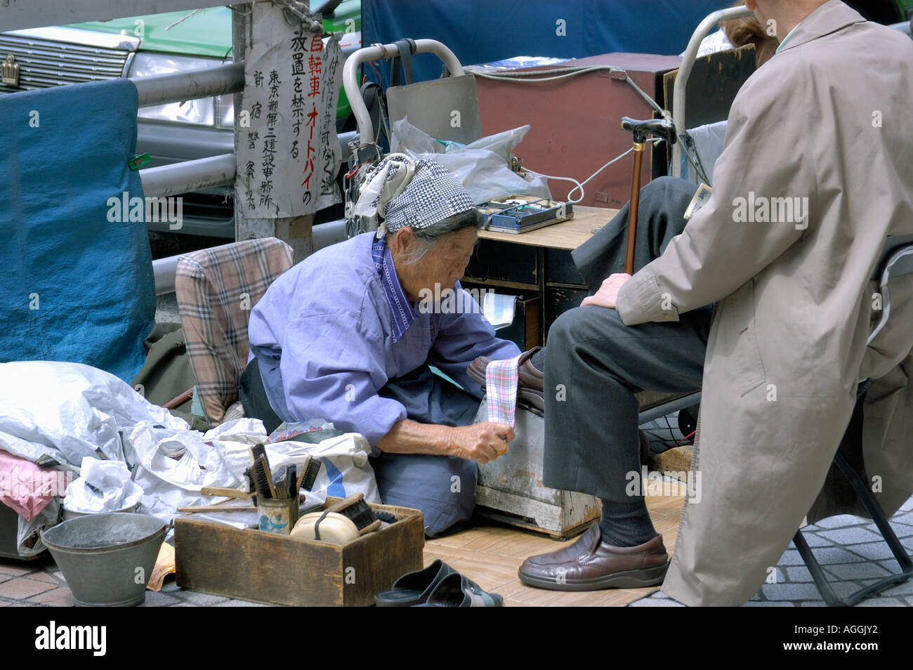 old woman polishing shoes, Tokyo, Japan - Stock Image