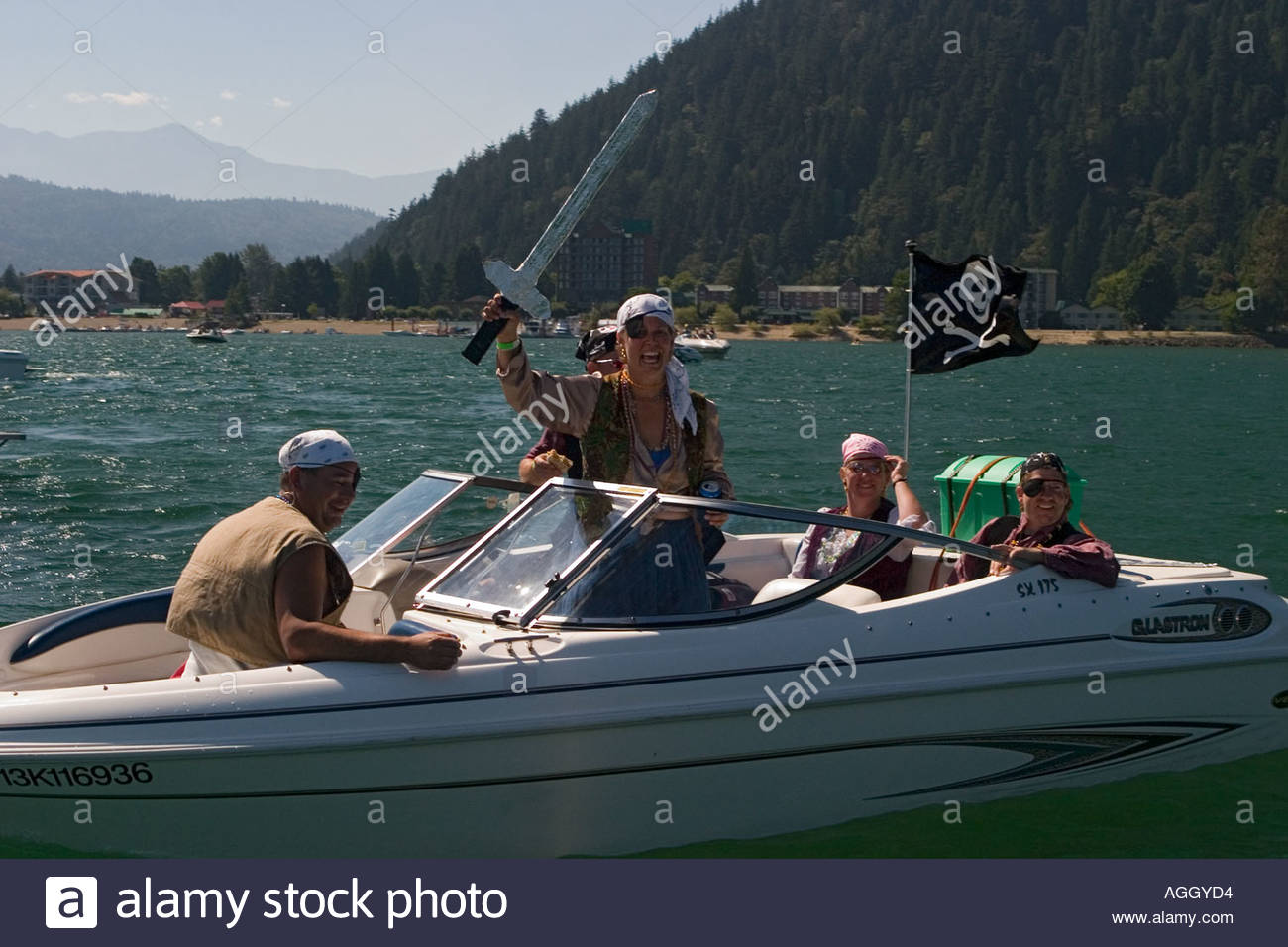 Speedboat carrying people who are dressed as pirates - Stock Image