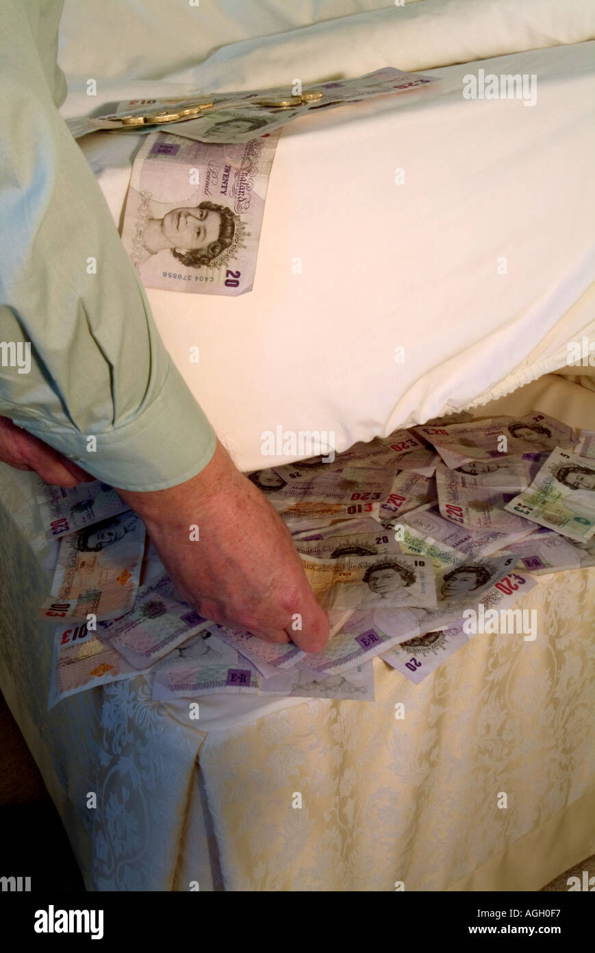 Cash In Hand Pound Sterling Bank Notes Being Placed Under Bed Stock Photo Alamy
