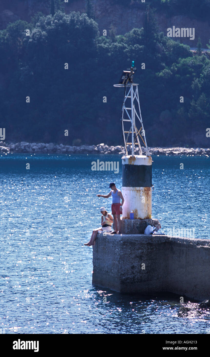 Couple fishing off harbour arm Poros Kefalonia Greece Poros is the second largest port in Kefalonia Mediterranean Sea - Stock Image
