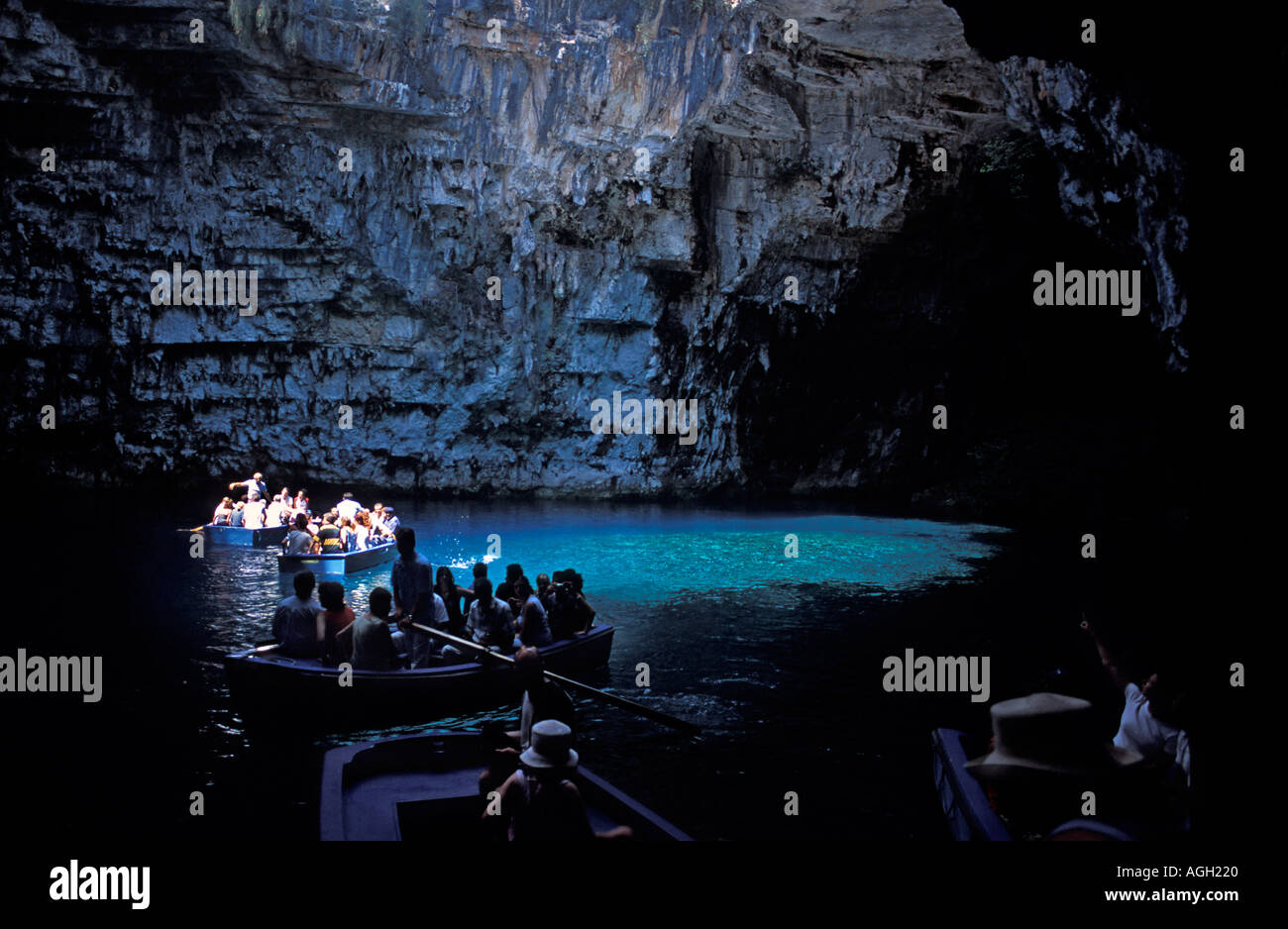 Tourists on a boat tour of Melissani Lake and cave Crystal blue waters of underground lake Kefalonia Ionian Islands Greece - Stock Image