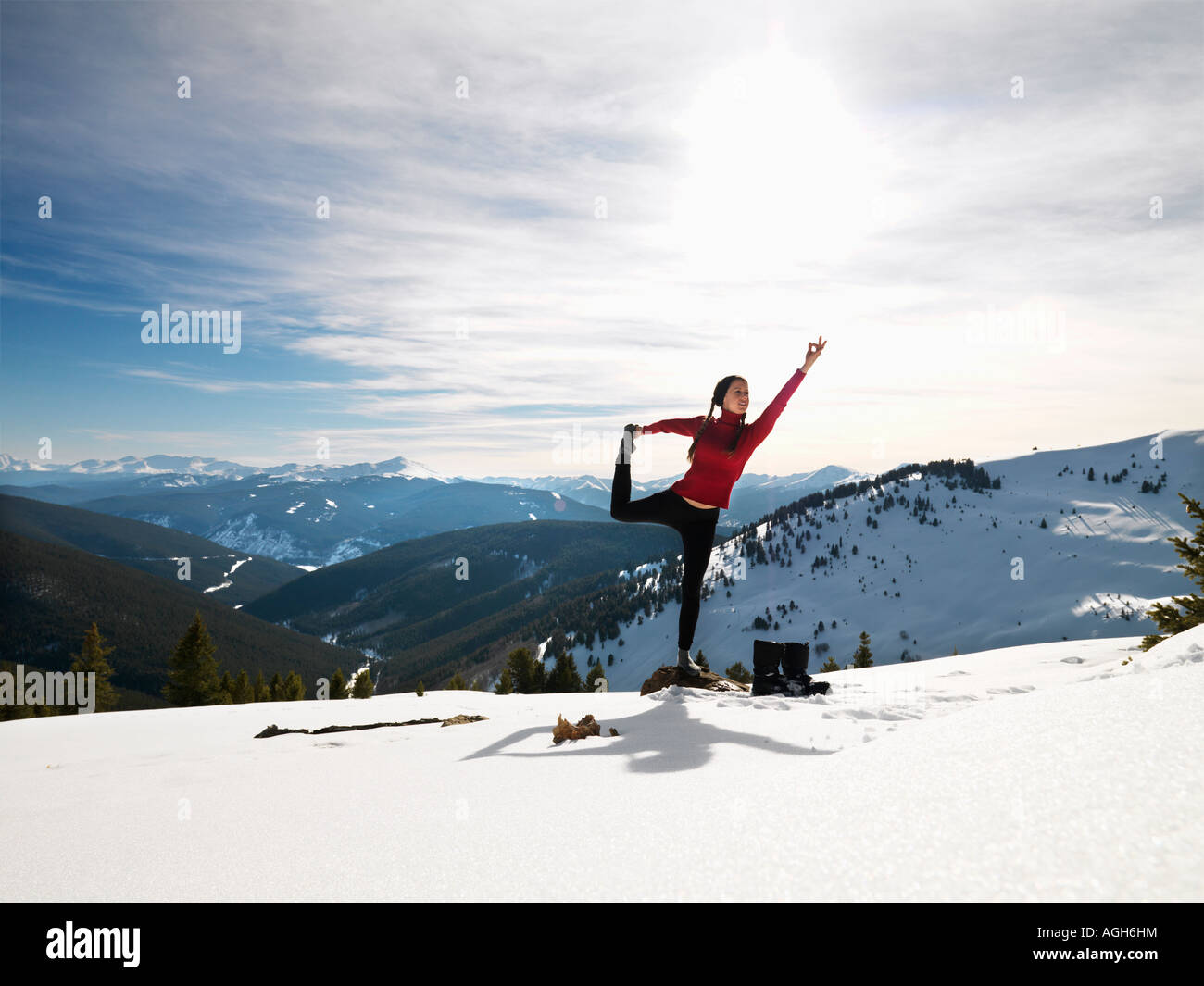 Young woman doing yoga pose on rock in snow in mountainous terrain - Stock Image