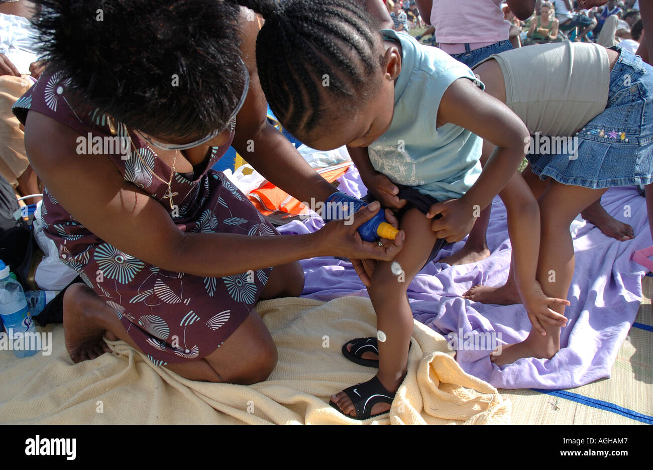 Mother putting suncream on child - Stock Image