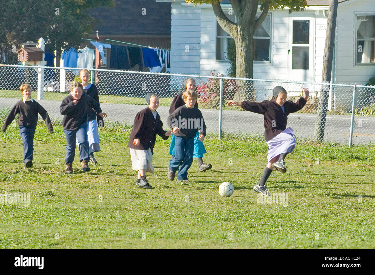 Children play school yard soccer at recess Amish life in Millersburg and Sugar Creek Holms County Ohio - Stock Image