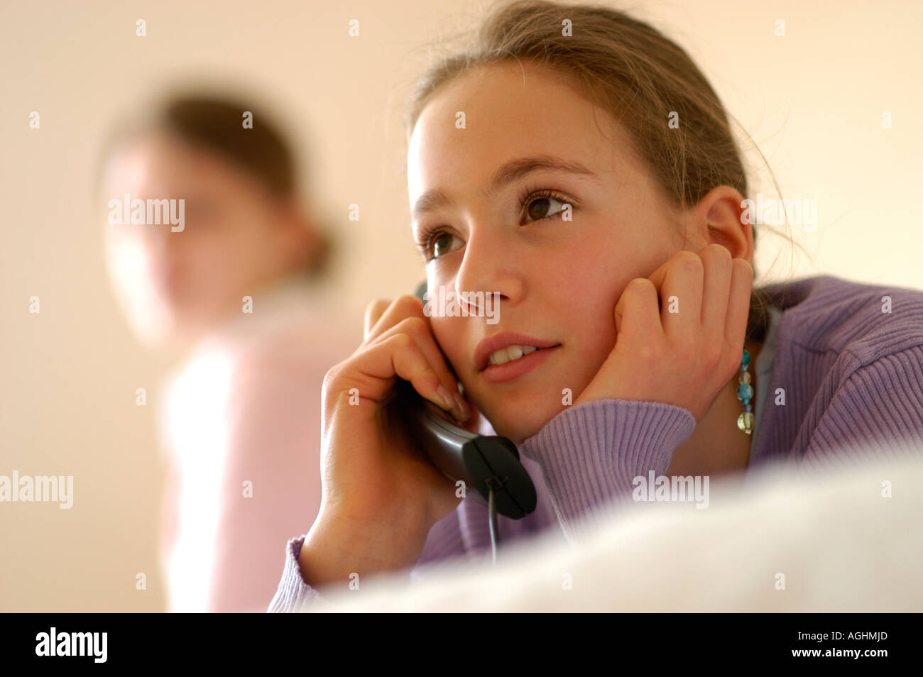 Teenage girl looking at friend talking on phone Stock Photo
