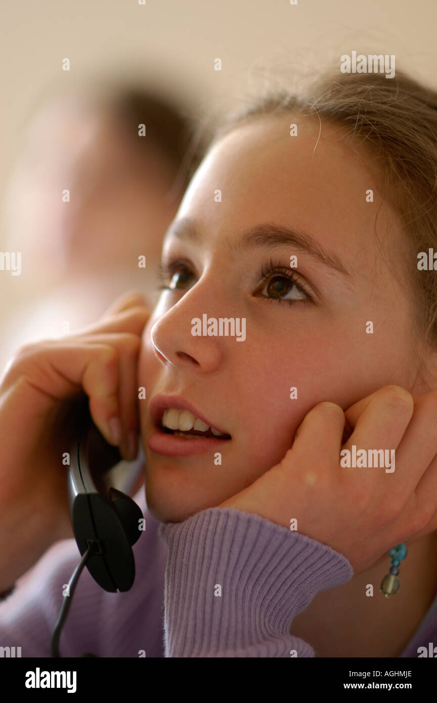 Teenage girl looking at friend talking on phone close up - Stock Image