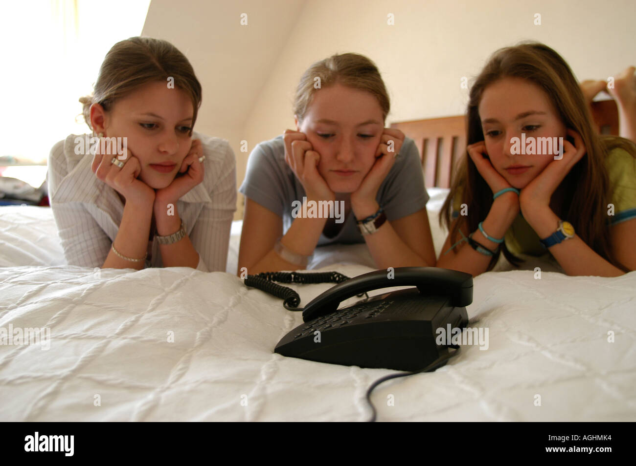 Teenage girls with hand on chin starring at telephone - Stock Image