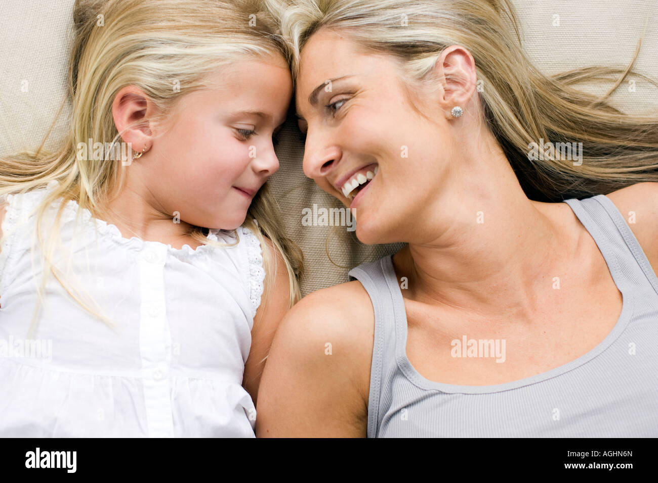 mother and daughter lying down smiling at eachother - Stock Image