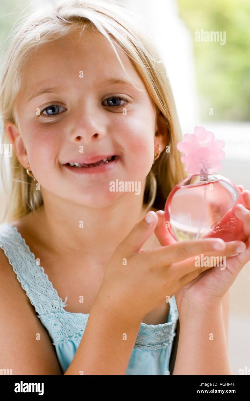 little girl holding up a child s perfume bottle Stock Photo