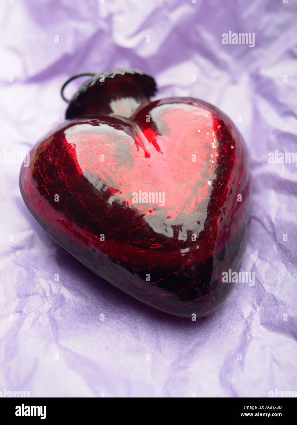 red heart shaped glass ornament laying on purple paper stock photo