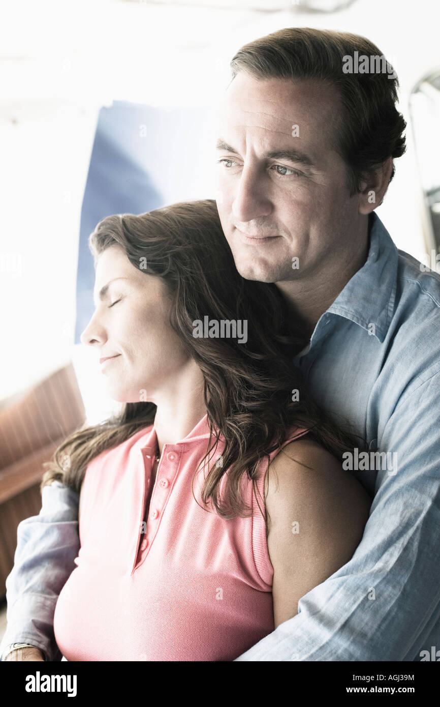 Mid adult man embracing a mid adult woman from behind - Stock Image
