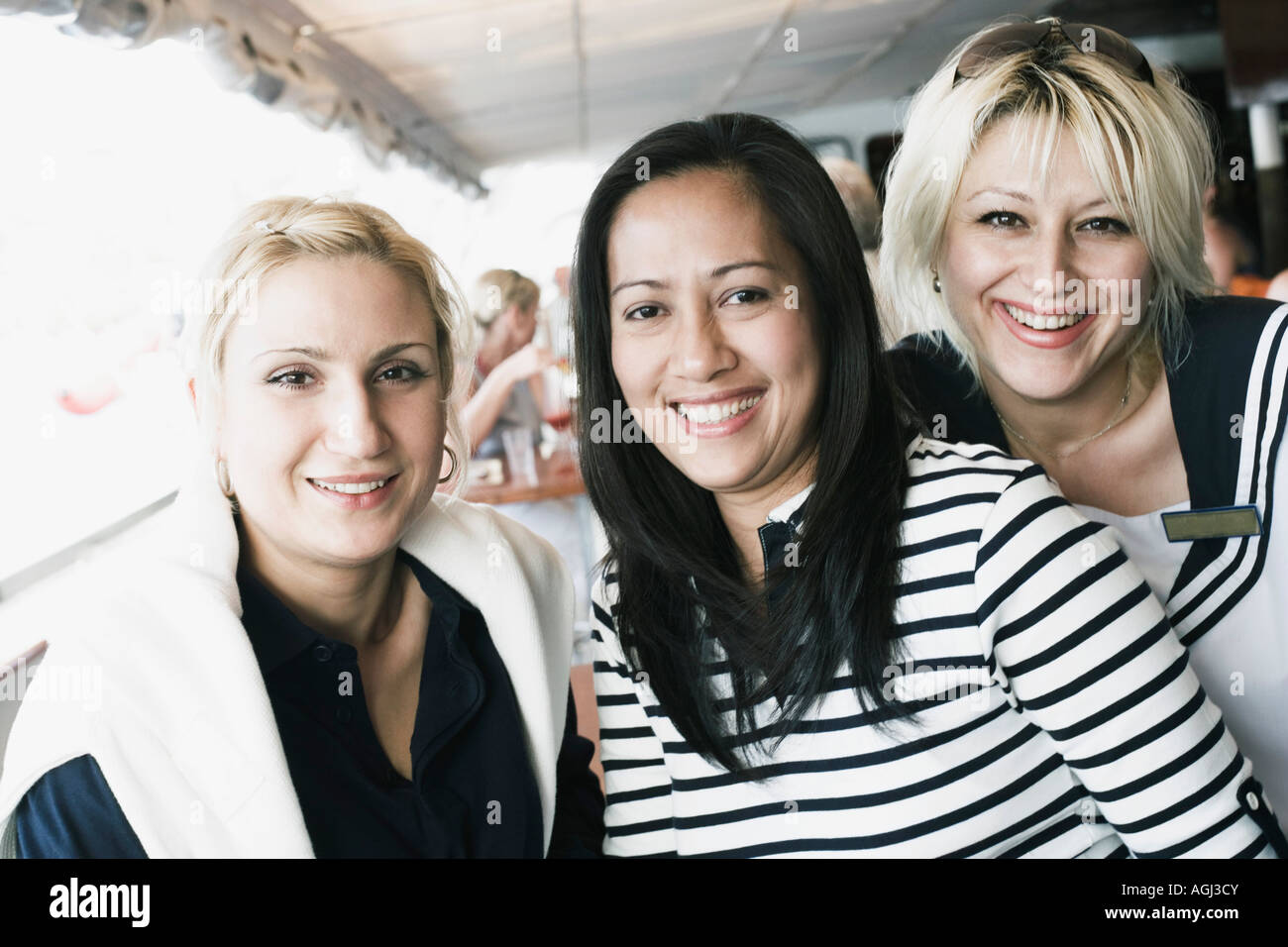 Portrait of three friends smiling - Stock Image