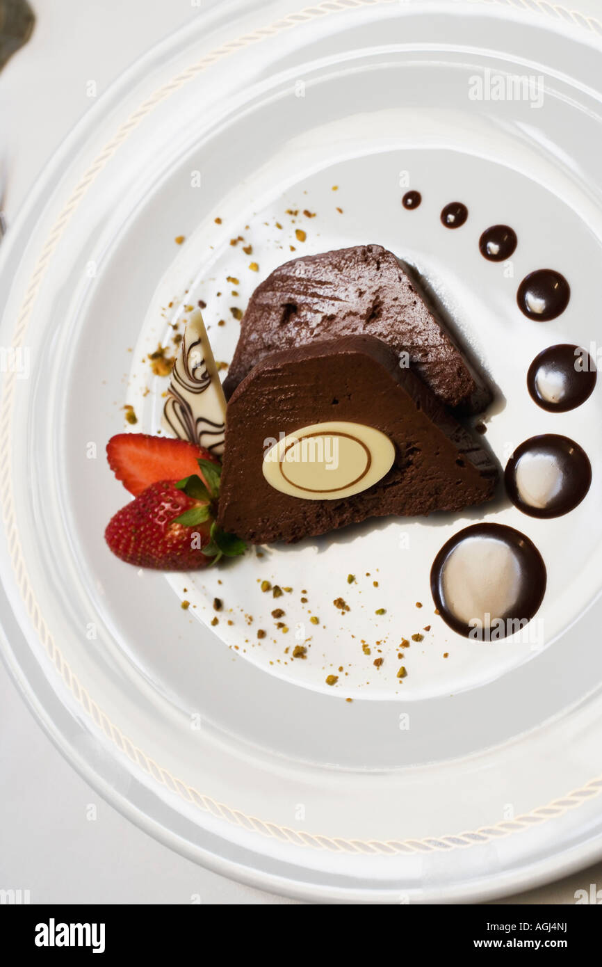 Close-up of two slices of chocolate cake with a strawberry in a plate - Stock Image