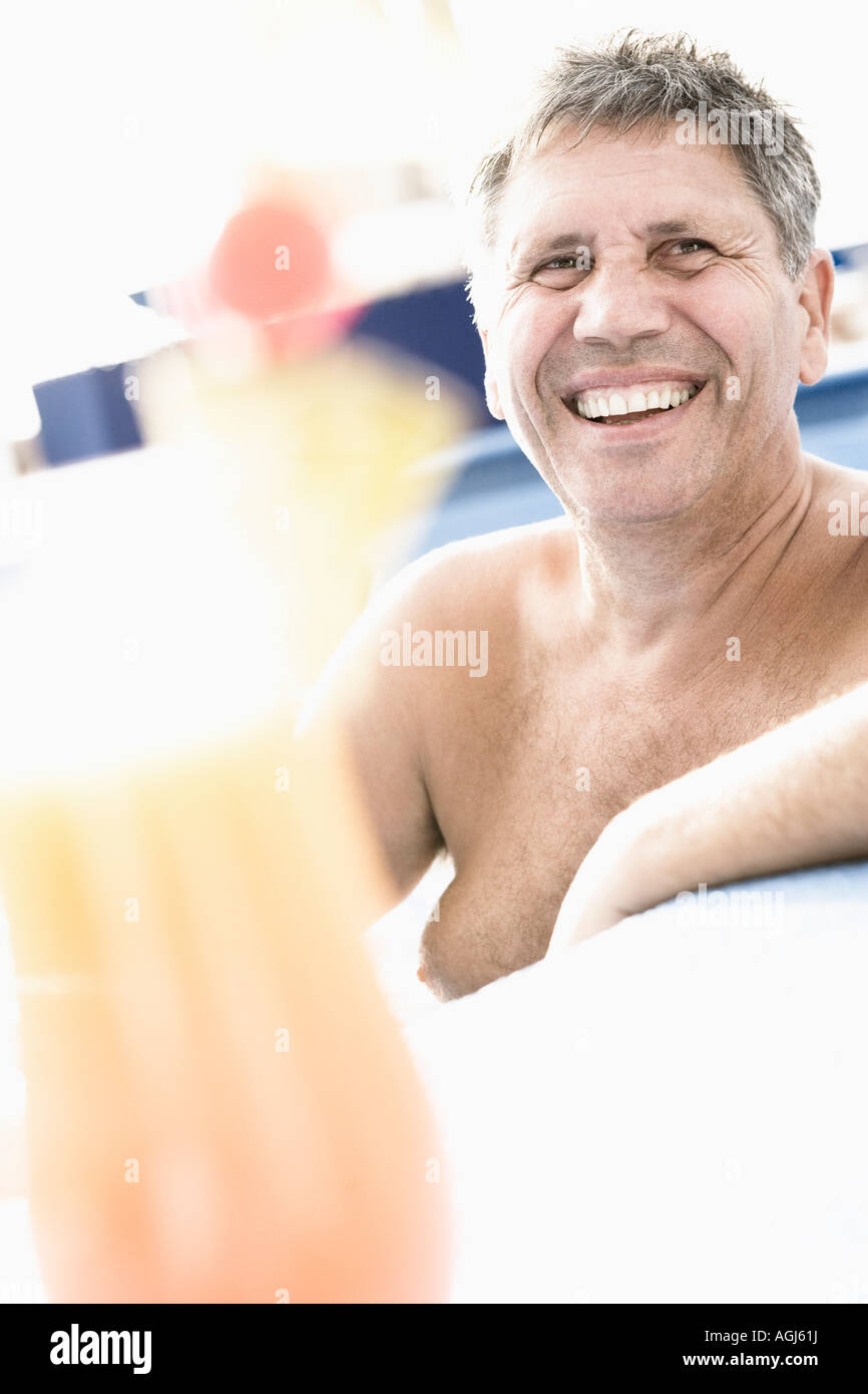 Senior man smiling in a swimming pool - Stock Image
