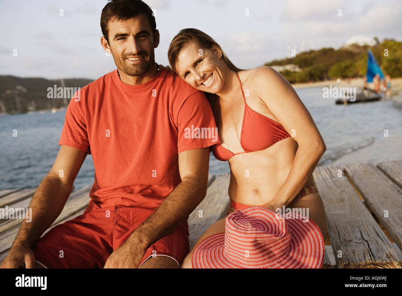 Portrait of a mid adult couple sitting on a pier and smiling - Stock Image