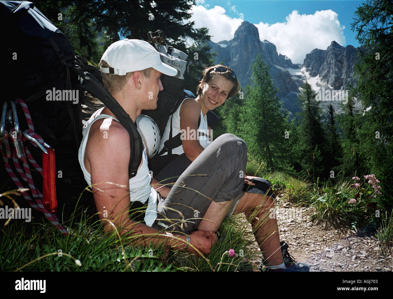 Italy Alps Dolomiti mountains young hikers couple takes a rest on a hike - Stock Image