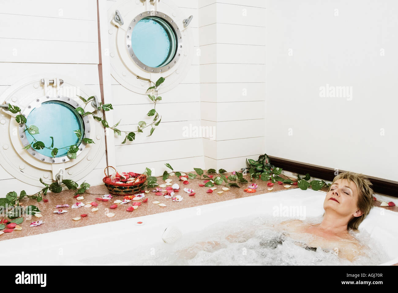 Mature woman in a bathtub - Stock Image