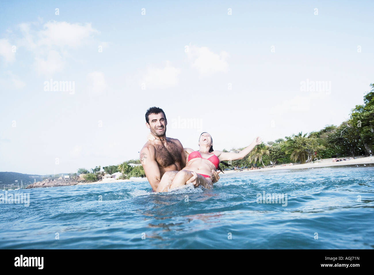 Mid adult man carrying a mid adult woman in water - Stock Image