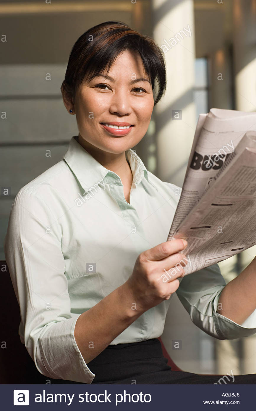 Businesswoman with newspaper - Stock Image
